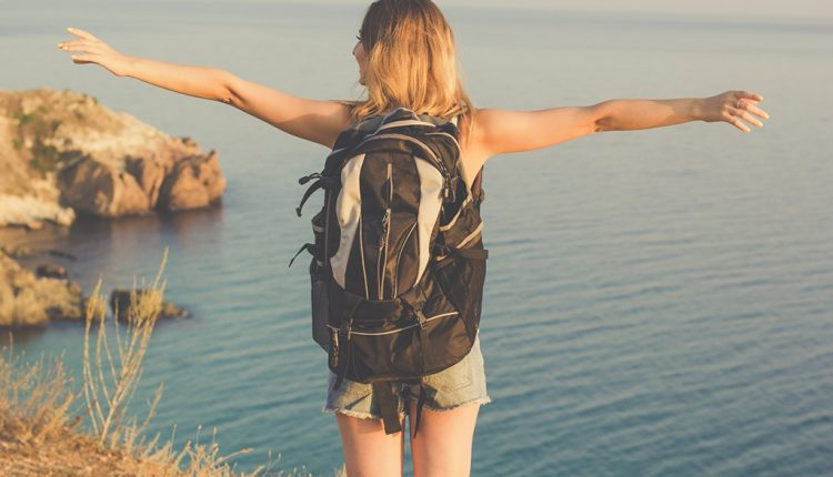 Back view of backpacker teen girl is standing on rock
