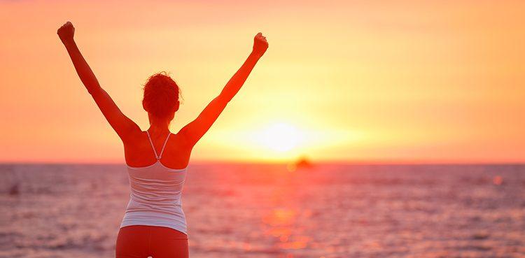 Happy cheering celebrating success woman at beautiful beach suns